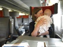 Chéri de fixation de mère sur le train Images stock