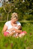 Chéri de soins de mère sur le pré Image stock