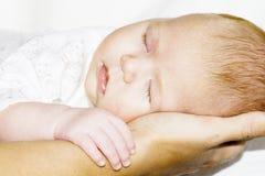 Chéri de sommeil sur des mains d'une mère Photos stock