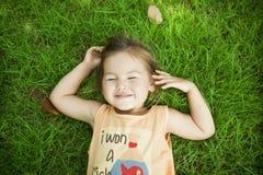 Chéri de sourire se trouvant sur l'herbe photographie stock