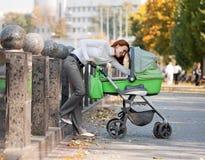 Chéri de transport de jeune mère en stationnement d'automne Images libres de droits