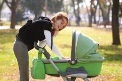 Chéri de transport de jeune mère en stationnement d'automne Image stock
