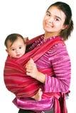 Chéri de transport de jeune mère moderne dans une élingue image libre de droits