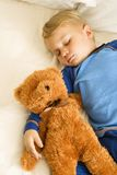 Chéri dormant avec l'ours. Photographie stock libre de droits