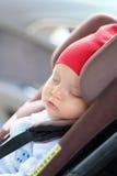 Chéri dormant dans le siège de véhicule Photographie stock libre de droits
