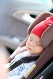 Chéri dormant dans le siège de véhicule Image libre de droits