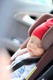 Chéri dormant dans le siège de véhicule Images stock