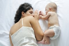 Chéri dormant près de sa mère Images stock