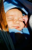 Chéri dormant sur les mains de la mère images stock