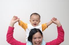 Chéri heureuse sur les épaules de la mère image libre de droits