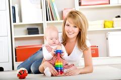 Chéri jouant avec des jouets avec la mère heureuse Photographie stock libre de droits