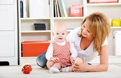 Chéri jouant avec des jouets avec la mère heureuse Photos libres de droits