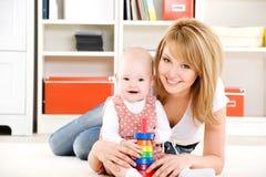 Chéri jouant avec des jouets avec la mère heureuse Photos stock