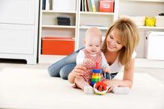 Chéri jouant avec des jouets avec la mère heureuse Image stock