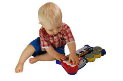 Chéri jouant avec le piano de jouets Photographie stock