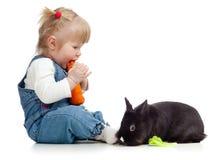 Chéri mangeant d'un lapin de raccord en caoutchouc et de alimenter photographie stock