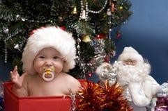 Chéri mignonne dans le chapeau rouge devant l'arbre de Noël Image stock