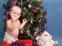 Chéri mignonne devant l'arbre de Noël Photos stock
