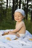 Chéri mignonne s'asseyant sur l'herbe Images libres de droits