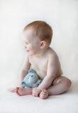 Chéri mignonne s'asseyant vers le haut avec un jouet Images libres de droits