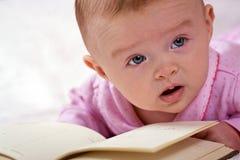 Chéri nouveau-née avec un livre Images libres de droits