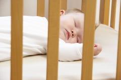 Chéri nouveau-née dans le lit de camp photos stock
