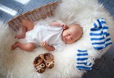 Chéri nouveau-née de sommeil dans le panier sur la basane photo libre de droits