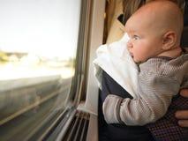 Chéri regardant à l'extérieur l'hublot de train Images libres de droits