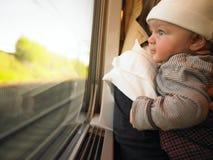 Chéri regardant à l'extérieur l'hublot de train Image libre de droits
