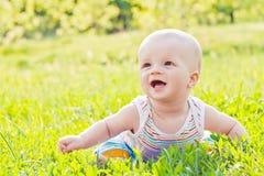 Chéri riante heureuse s'asseyant sur l'herbe Photos libres de droits