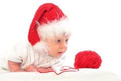Chéri sérieuse dans le chapeau rouge de Noël avec une boucle rouge Photographie stock libre de droits