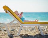 Chéri s'étendant sur l'eau sunbed et potable Photo stock