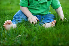 Chéri s'asseyant dans l'herbe Photo stock