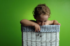 Chéri s'asseyant dans un panier photos stock