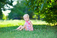 Chéri s'asseyant sur l'herbe verte photographie stock