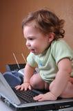 Chéri s'asseyant SUR l'ordinateur portatif souriant à l'écran Photographie stock libre de droits