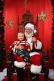 Chéri s'asseyant sur les genoux de Santa Image stock