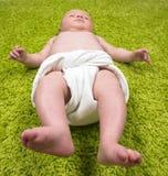 Chéri se trouvant sur le tapis vert Photographie stock