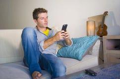 Chłodno atrakcyjny i szczęśliwy mężczyzna obsiadanie przy żywym izbowym kanapy leżanki networking relaksującym cieszący się inter Zdjęcia Royalty Free