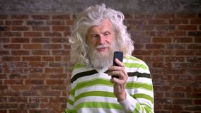 Chłodno caucasian starszy mężczyzna z wielkim białym kędzierzawym włosy i ładną brodą ma wideo wezwanie i opowiada spokojnie podc zdjęcie wideo