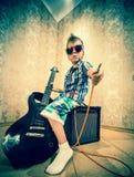 Chłodno chłopiec pozuje z gitarą elektryczną Obrazy Royalty Free