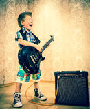 Chłodno chłopiec pozuje z gitarą elektryczną Fotografia Royalty Free