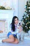 Chłodno dziewczyna przyglądająca i ono uśmiecha się przy kamerą, siedzi blisko psa wewnątrz Obrazy Stock