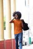 Chłodno facet opowiada na telefonu komórkowego przewożenia torbie w miasteczku Fotografia Royalty Free