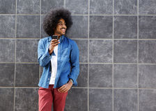 Chłodno facet z afro używa telefonem komórkowym Fotografia Stock