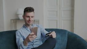 Chłodno faceta zakup online w domu z telefonu komórkowego i banka kartą Elegancki ambitny mężczyzna płaci rachunki lub rozkaz now zdjęcie wideo