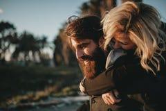 Chłodno indie para ma zabawę outdoors podczas gdy daje ona piggyback fotografia stock