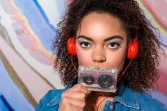 Chłodno kobiety przesłuchania piosenka i utrzymywać kaseta Fotografia Royalty Free
