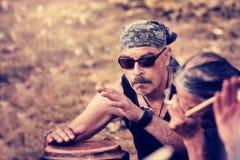 Chłodno Latynoski wieka średniego percussionist jest ubranym bandanna bawić się rytm z djembe bębenu bongo zdjęcia royalty free