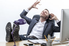 Chłodno męski przedsiębiorca śmia się na telefonie z ciekami na biurku Obraz Stock